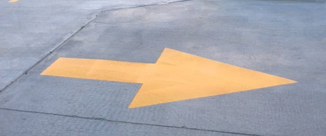 Yellow Directional Arrow Painted In Parking Lot